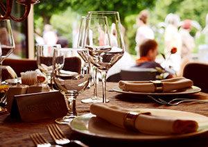 Fokusā servētas divas vīna glāzes, divas dzērienu glāzes, šķīvji ar salvetēm un galda piederumi. Fonā cilvēki brīvā dabā