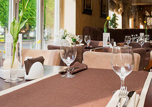 Vairāki galdiņi ar brūnu galdautu restorānā ar servētām vīna glāzēm