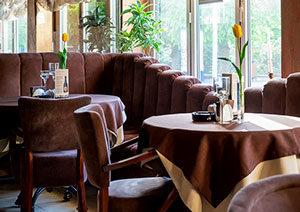 Divi apaļi restorāna galdiņi, vāzē pa dzeltenai tulpei, blakus krēsli un stūra dīvāns