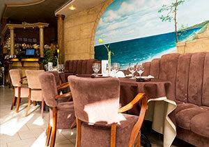 Divi mīksta polsterējuma krēsli, pie apaļa galdiņa ar brņu galdautu, fonā fototapete ar jūras krastu