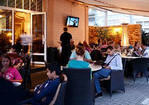 pie galdiņiem terasē sēž cilvēki un lasa ēdienkartes, fonā restorāna siena