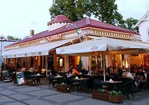 Pie galdiņiem sēdoši cilvēki un restorāna terase ar nojumēm